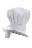 Le chapeau d'un chef avec faire cuire des knifes Photographie stock libre de droits