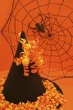Le chapeau de la sorcière avec la toile d'araignée et le maïs de sucrerie Photos stock