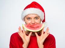 Le chapeau de Santa d'usage de fille mangent le fond de blanc de pastèque de tranche Festins d'été sur la fête de Noël Concept ex photographie stock