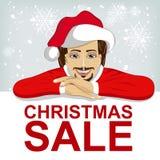 Le chapeau de Santa de wearnig de jeune homme s'est penché sur le conseil vide avec le texte rouge de vente de Noël Photos stock