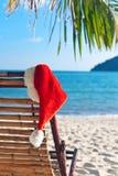 Le chapeau de Santa rouge s'arrêtant sur la présidence de plage image libre de droits