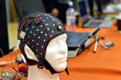 Le chapeau de tête de l'électroencéphalogramme EEG avec les électrodes plates de disques en métal attachées aux model's en plas Image libre de droits