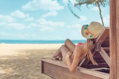 Le chapeau du soleil de petit morceau de jeune femme détendant sur le mauvais du soleil apprécie le bain de soleil à la plage ave photographie stock libre de droits