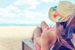Le chapeau du soleil de petit morceau de jeune femme détendant sur le mauvais du soleil apprécie le bain de soleil à la plage ave image libre de droits