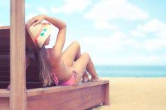 Le chapeau du soleil de petit morceau de jeune femme se trouvant sur le mauvais du soleil apprécie le bain de soleil à la plage a image stock