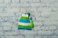 Le chapeau et les espadrilles de bébé sécheront sur une corde sur un mur de briques blanc Image libre de droits