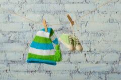 Le chapeau et les espadrilles de bébé sécheront sur une corde sur un mur de briques blanc Images stock