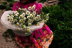 Le chapeau et les marguerites, la fille présente un bouquet Image stock