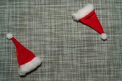 Le chapeau rouge de Santa de décoration de Noël sur la fin grise de fond de tissu  photo stock