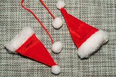 Le chapeau rouge de Santa de décoration de Noël sur la fin grise de fond de tissu  images libres de droits
