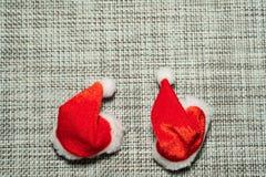 Le chapeau rouge de Santa de décoration de Noël sur la fin grise de fond de tissu  image libre de droits