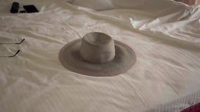 Le chapeau se trouvant sur le lit dans la chambre d'hôtel Femme méconnaissable dormant à l'arrière-plan dans un lit confortable t banque de vidéos