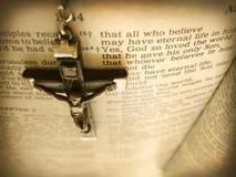 Le chapelet fait main Crucific accroche au-dessus du vers de bible de la vue du ciel Image stock