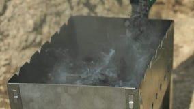 Le charbon de bois a mis dans le brasero avec un feu de flambage banque de vidéos