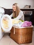 Le chargement blond heureux de femme vêtx dans la machine à laver photos stock