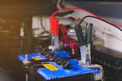 Le chargement de batterie câble la puissance de transfert, homme appelant au service de mécanicien de voiture photo libre de droits