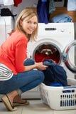 Le chargement de femme vêtx dans la machine à laver Photographie stock