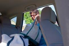 Le chargement supérieur de femme met en sac dans un véhicule Photographie stock libre de droits