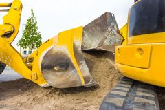 Le chargeur d'embout avant vidant la pierre et le sable dans une exploitation extraient photos stock