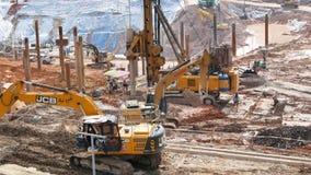 Le chargeur d'excavatrice aux travaux en mouvement de sol dans le chantier de construction, travailleur peut fonctionnement vu au banque de vidéos