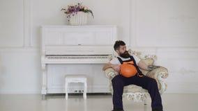 Le chargeur fatigué se repose sur le fauteuil, ayant le repos d'isolement sur le blanc Fond de piano D'isolement sur le blanc Int banque de vidéos