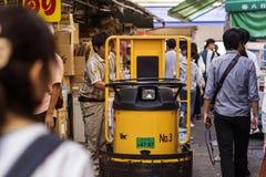 Le chargeur met la boîte au chariot élévateur dans la foule photos libres de droits