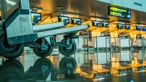 Le chariot de bagage/chariot devant signent le contre- bureau à l'intérieur du bâtiment d'aéroport Photo stock