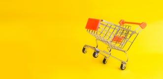 Le chariot de supermarché se tient sur un fond jaune Le concept des achats et la vente, les affaires et le commerce L'humeur de a photo stock