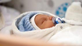 Le chariot en gros plan de portrait de beau bébé de sommeil a tiré de la main sur une profondeur de visage nouveau-né de bébé de  banque de vidéos