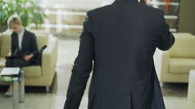 Le chariot a tiré des jambes de l'homme d'affaires marchant par le lobby d'hôtel tirant le bagage et parlant au téléphone portabl clips vidéos