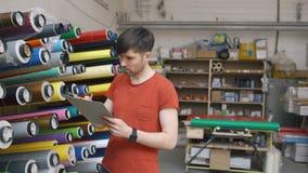Le chariot a tiré du jeune travailleur dans l'entrepôt avec le presse-papiers vérifiant l'inventaire L'homme travaille au service