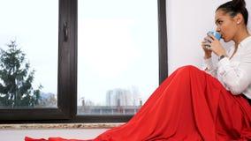 Le chariot a tiré le mouvement lent de la femme couvert de couverture rouge se reposant à côté d'un thé potable de grande fenêtre clips vidéos
