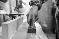 Le charpentier affile un burin dans un petit atelier image libre de droits