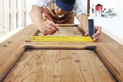 Le charpentier au travail mesure avec l'équerre et le crayon sur le bois image stock