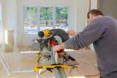 Le charpentier au travail utilisant la circulaire a vu couper la plinthe en bois de bâtis photographie stock