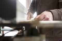 Le charpentier coupant un morceau avec la circulaire électrique a vu au-dessus de la table Photos stock