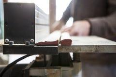 Le charpentier coupant un morceau avec la circulaire électrique a vu au-dessus de la table Photographie stock