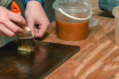 Le charpentier couvre les pièces en bois de meubles de la cire en bois images libres de droits
