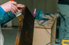 Le charpentier couvre les pièces en bois de meubles de la cire en bois photographie stock