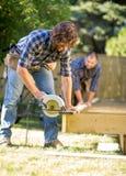 Le charpentier Cutting Wood With tenu dans la main a vu tandis que Image stock