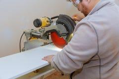Le charpentier d'homme à l'aide de l'électro circulaire a vu couper les étagères blanches stratifiées photo stock