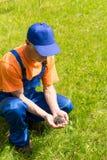 Le charpentier dans l'équipement fonctionnant bleu tient une pile des vis Images libres de droits