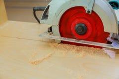 Le charpentier employant la circulaire a vu couper le conseil en bois dans l'atelier en bois Photos stock