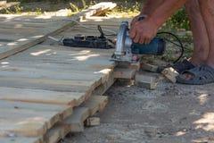 Le charpentier employant la circulaire a vu pour couper les conseils en bois image stock