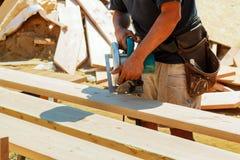 Le charpentier employant la circulaire a vu pour couper les conseils en bois Coordonnées de construction du travailleur de sexe m Photographie stock