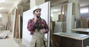 Le charpentier en chef dans l'uniforme de menuiserie et un casque blanc répond à l'appel téléphonique banque de vidéos