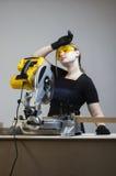 Le charpentier féminin fatigué avec un disque circulaire a vu Images stock