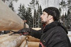 Le charpentier fait des marques boiser extérieur, utilisant des rondins traçant l'outil Images libres de droits