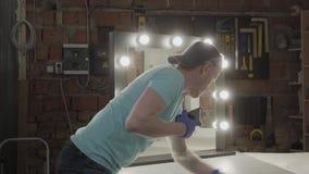 Le charpentier a fini de faire les ampoules dans le miroir pour le client et de nettoyer la surface Les lumi?res sont allum?es Co banque de vidéos