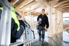Le charpentier Holding Drill Machine tout en regardant le collègue portent Image stock